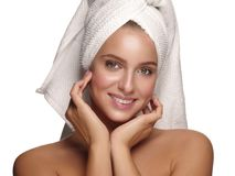 Portrait of a young healthy and beautiful girl with a towel on her head doing daily skincare after shower. White background royalty free stock image