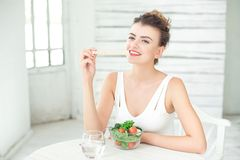 Portrait of a young healthy woman eating a crispbread in white room. Stock Photo