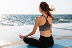 Portrait of young healthy woman sitting in lotos pose while prac. Ticing meditation at seaside Royalty Free Stock Image