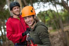 Young hiker couple holding zip line in forest during daytime. Portrait of young hiker couple holding zip line in forest during daytime stock images