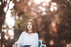 Portrait of young hipster Asian girl posing in the autume park forest bokeh background Stock Photos