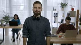 Portrait of young hipster with beard at workplace stock video