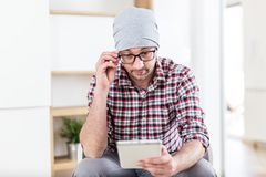 Portrait of young hipster businessman sitting at the office and using digital tablet royalty free stock photo