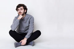 A portrait of young hipster with fair skin and trendy beard sitting on the floor crossed legs. Handsome man with nice face feature stock photography