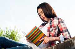 Portrait of young hipster female reading book in the park. Portrait of young hipster female reading book and spending freetime in the park Royalty Free Stock Image