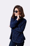 A portrait of young hipster girl dressed in stylish shirt and jeans round sunglasses holding her hand under chin looking seriously Royalty Free Stock Photography