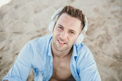 Portrait of Young hipster man in a blue shirt and jeans listening to music in headphones on a smartphone and is sitting. On beach.Digital Music lounge and royalty free stock image