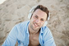Portrait of Young hipster man in a blue shirt and jeans listening to music in headphones on a smartphone and is sitting. On beach.Digital Music lounge and stock images