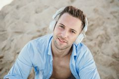 Portrait of Young hipster man in a blue shirt and jeans listening to music in headphones on a smartphone and is sitting. On beach.Digital Music lounge and royalty free stock photos