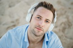 Portrait of Young hipster man in a blue shirt and jeans listening to music in headphones on a smartphone and is sitting. On beach.Digital Music lounge and royalty free stock photo