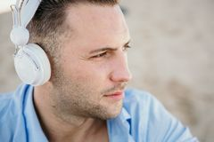 Portrait of Young hipster man in a blue shirt and jeans listening to music in headphones on a smartphone and is sitting. On beach.Digital Music lounge and stock image