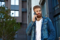 Portrait of young hipster man in front of office building using her cell phone royalty free stock photo