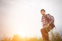 Portrait of young hipster man outdoor raising hands with backpac. K on his shoulder, Adventure tourism Royalty Free Stock Image