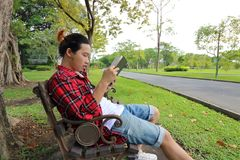 Portrait of young hipster man reading a book on the bench in beautiful outdoor park. Wide angle shot royalty free stock photography