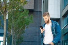 Portrait of young hipster man reading message on the street. stock images