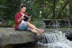 Portrait of young hipster man in red shirt reading a book in beautiful nature background. Royalty Free Stock Photography