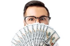 Portrait of a young hipster man standing isolated on a white background holding money. stock images