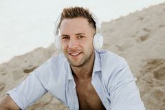 Portrait of Young hipster man in a white shirt and jeans listening to music in headphones on a smartphone and is sitting. On beach.Digital Music lounge and royalty free stock image