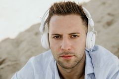 Portrait of Young hipster man in a white shirt and jeans listening to music in headphones on a smartphone and is sitting. On beach.Digital Music lounge and stock photos