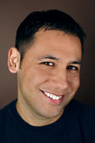 Portrait of a young hispanic man. Smiling on a brown background Stock Image
