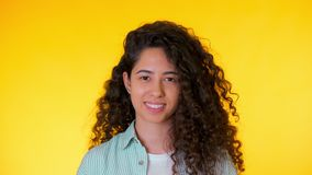 Portrait of young hispanic student girl with curls on yellow background. Trendy cute woman smiling to camera. Studio. Footage. Female in shirt, casual style stock video