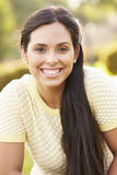 Portrait Of Young Hispanic Woman Sitting In Park Royalty Free Stock Images
