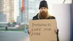 Portrait of young homeless man with cardboard looking at camera and very upset because of immigrants crisis in Europe stock video