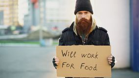 Portrait of young homeless man with cardboard looking at camera and wants to work for food looking at camera at street. Portrait of young homeless man with Stock Photos