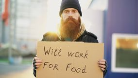 Portrait of young homeless man with cardboard looking at camera and wants to work for food looking at camera at street. Portrait of young homeless man with Stock Images