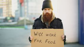 Portrait of young homeless man with cardboard looking at camera and wants to work for food looking at camera at street. Portrait of young homeless man with Stock Photography