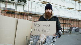 Portrait of young homeless man with cardboard looking at camera and wants to work for food standing near shopping cart stock video footage