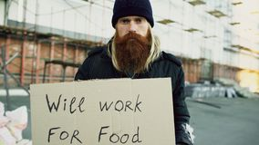 Portrait of young homeless man with cardboard looking at camera and wants to work for food standing near shopping cart. Portrait of young homeless man with Stock Photography