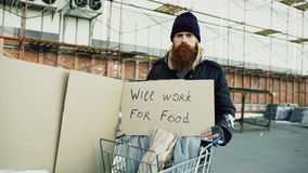 Portrait of young homeless man with cardboard looking at camera and wants to work for food standing near shopping cart. Portrait of young homeless man with Stock Images