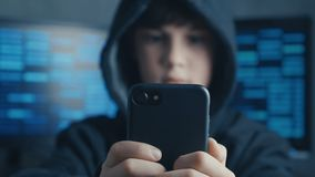 Young hooded boy using a smartphone device at data center. Portrait of Genius boy wonder hacks system at cyberspace.