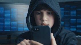 Young hooded boy using a smartphone device. Portrait of Genius boy wonder hacks system at cyberspace.