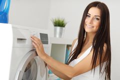 Portrait of young housewife with laundry next to washing machine Stock Photography