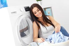 Portrait of young housewife with laundry next to washing machine Stock Photos