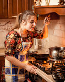 Portrait of young housewife tasting soup from pan on fire Stock Images