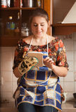 Portrait of young housewife using tablet while cooking Royalty Free Stock Image