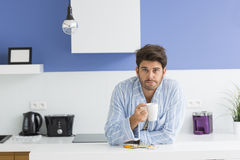Portrait of young ill man holding coffee mug while leaning on kitchen counter Royalty Free Stock Images
