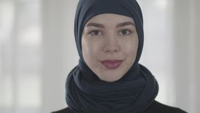 Portrait of independent young muslim woman looking serious confident at camera wearing traditional headscarf. Close up stock video footage