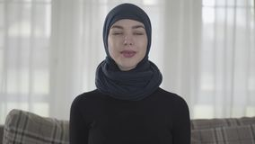 Portrait of independent young muslim woman looking serious confident at camera wearing traditional headscarf stock video footage