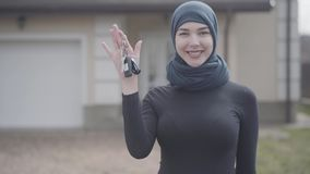 Portrait of independent successful confident smiling young muslim woman holding and waving car keys wearing traditional. Portrait of young independent smiling stock video footage
