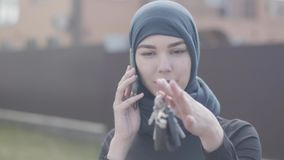 Portrait of independent smiling young muslim woman talking bey phone and holding car keys wearing traditional headscarf. Portrait of young independent smiling stock footage