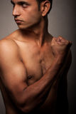 Portrait of young Indian angry man over dark  Stock Photography