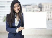 Portrait of a young Indian businesswoman holding sign Stock Photo