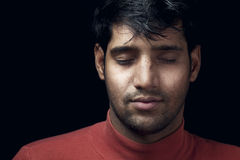Portrait of young Indian  man closed eyes over dark Stock Image