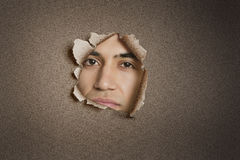 Portrait of a young Indian man peeking from ripped paper hole Royalty Free Stock Photography