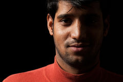 Portrait of young Indian  man smiling over dark Royalty Free Stock Photos