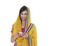 Portrait of young Indian woman in traditional wear holding cell phone against white background Stock Image